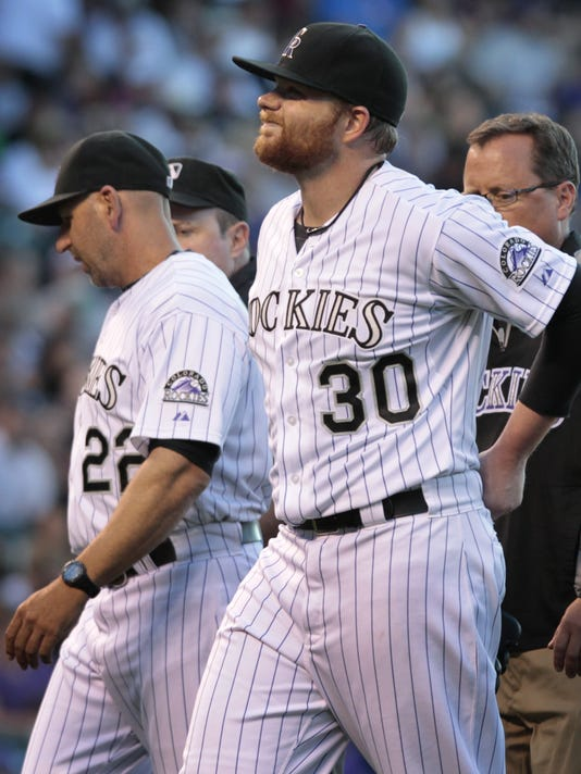 Colorado Rockies starting pitcher Brett Anderson (30) holds his back as he leaves a game against the Chicago Cubs in the fourth inning of a baseball game in Denver on Tuesday, Aug. 5, 2014.Rockies manager Walt Weiss (22) talks to home plate umpire umpire Marty Foster.(AP Photo/Joe Mahoney)