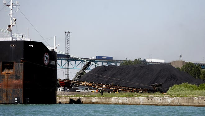 """A freighter loads up """"pet coke"""" along the along the Detroit River Wednesday, June 19, 2013."""