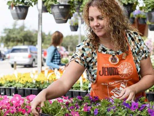 Female Home Depot employee arranges flowers.