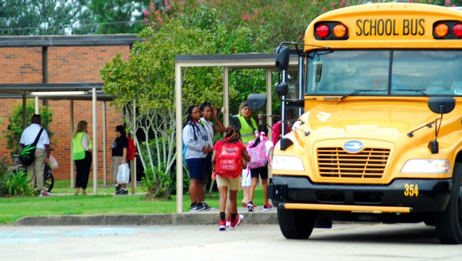 Students arrive at L.J. Alleman Middle on Aug. 11 for the first day of school. Classes were canceled for more than a week because of flooding. Schools are back in session Monday, Aug. 22.