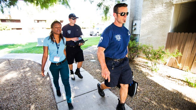 Ify Willson, a licensed behavioral-health specialist with Crisis Preparation and Recovery Inc., and Mesa Fire paramedics Rob Alkire (center) and Brian Davy approach an apartment where a woman was reportedly hallucinating. The team is part of a Mesa behavioral-health pilot program.
