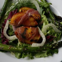 Prosciutto-wrapped grilled nectarines with asparagus and fennel on greens.