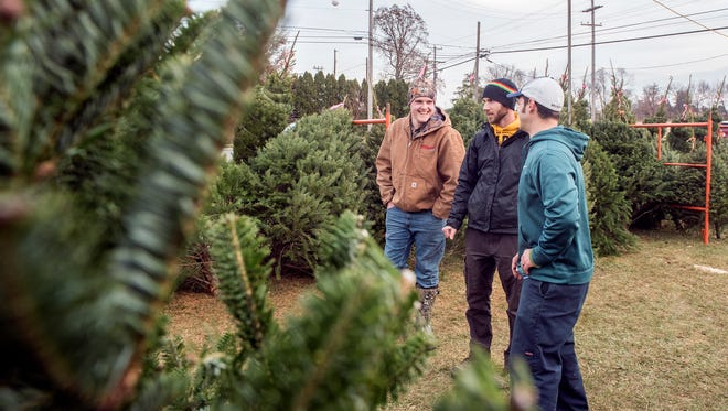 Mason Pflueger, from left, stands with Ben Neiderer and Ben Markle at the Neiderer family Christmas tree sales location, at Radio Road and High Street, Saturday, Dec. 2, 2017. The proceeds from the tree sales will help benefit Tommy Laudani and Nick Weaver, who are both battling with cancer.