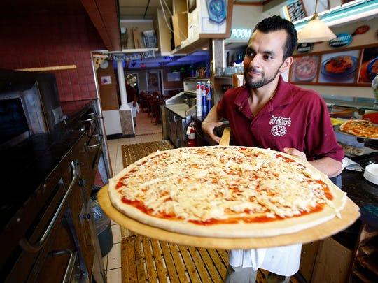 Kevin Durazzo prepares a pizza at Attilio's Restaurant & Pizzeria in Freehold Township.