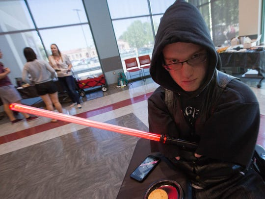 "William Morlan, dressed as a ""Dark Jedi"" poses with"