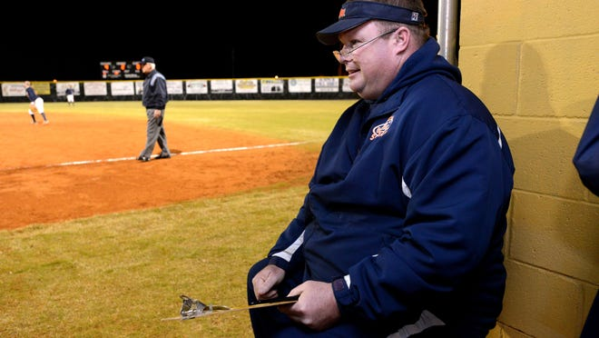 Escambia High School softball coach Mike Davis works from the dugout as the Gators take on the Milton Panthers.