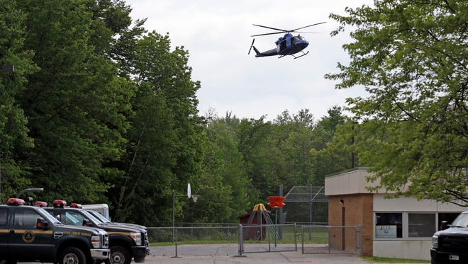 A helicopter lands briefly in the back yard of a community center in Dannemora, N.Y., Thursday, June 11, 2015.