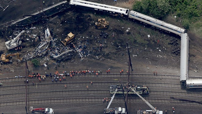 Investigators and first responders work near the wreckage of Amtrak Northeast Regional Train 188 from Washington to New York, which derailed May 12, 2015.
