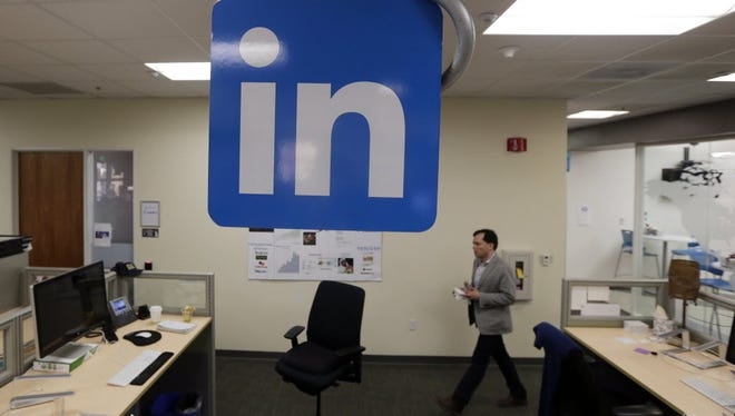n this Nov. 6, 2014 photo, a LinkedIn employee walks past a company logo at the company's headquarters in Mountain View, Calif.