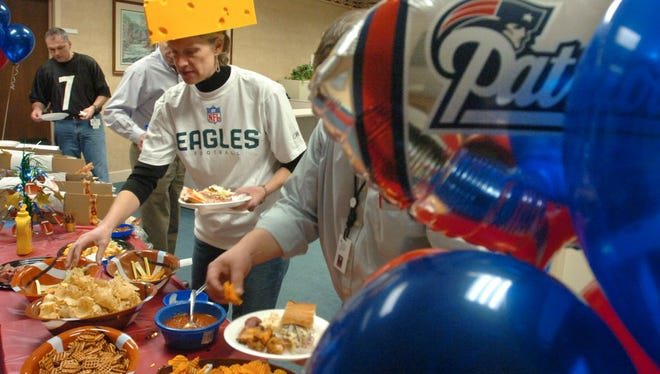 FILE - Laura Wand, the director of marketing for Johnson Controls, grabs up some lunch during a Super Bowl celebration where employees could wear whatever team jersey they wanted on Friday, Feb. 1, 2008.