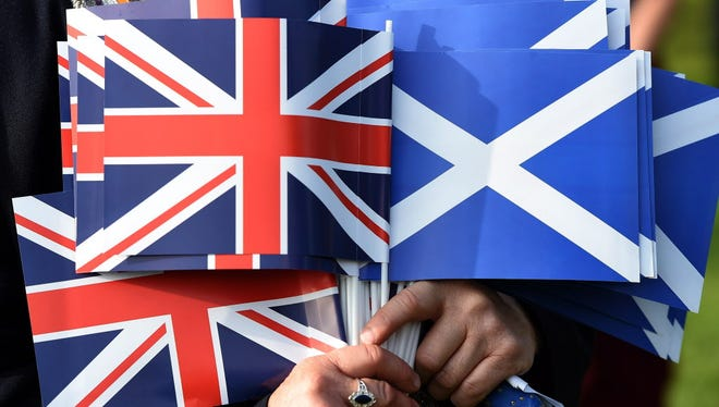A file picture dated 13 September 2014 shows a Unionist holding the Union jack (L) and the Saltire flag (R) during a march of the Orange Order, a Protestant fraternal organisation, in a show of solidarity for the Union of Britain in Edinburgh, Scotland.