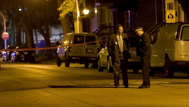 In this Friday, Nov. 18, 2016 photo, police clear a scene at 5600 South Princeton Ave., after Javon Wilson, 15, was shot and killed in the Englewood neighborhood of Chicago. The high school sophomore was the grandson of U.S. Rep. Danny Davis, D-Ill.