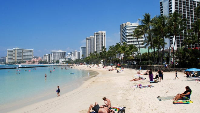 In this Monday, March 13, 2017, file photo, people relax on the beach in Waikiki in Honolulu. Many Americans might dream of going on vacation to places such as Waikiki, but a new poll shows nearly half of Americans won't be taking a summer vacation this year, mostly because they can't afford it and some because they can't get away from work.
