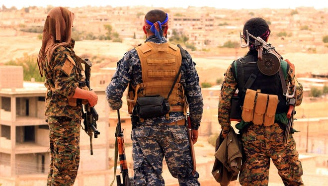 This file photo provided by the Syrian Democratic Forces (SDF) shows fighters from the SDF looking toward the northern town of Tabqa, Syria. The U.S.-led coalition headquarters in Iraq said in a written statement that a U.S. F-18 Super Hornet shot down a Syrian government SU-22 on Sunday, June 18, after it dropped bombs near the U.S. partner forces, known as the Syrian Democratic Forces. The shootdown was near the Syrian town of Tabqa. (Syrian Democratic Forces via AP, File)