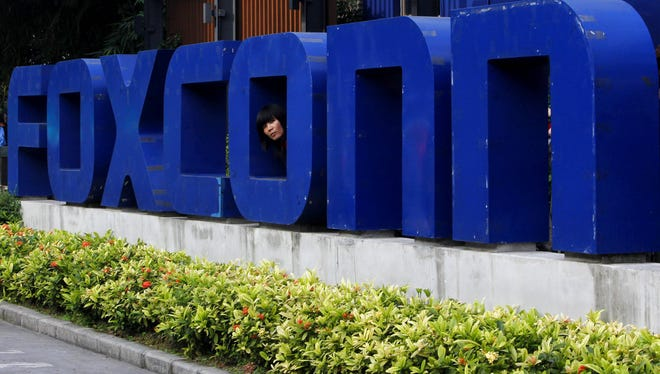 In this Thursday, May 27, 2010, file photo, a worker looks out through the logo at the entrance of the Foxconn complex in the southern Chinese city of Shenzhen.