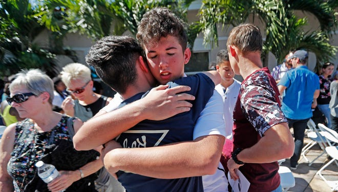 Students from Marjory Stoneman Douglas High School hug at the conclusion of a vigil at Parkland Baptist Church on Feb. 15, 2018.