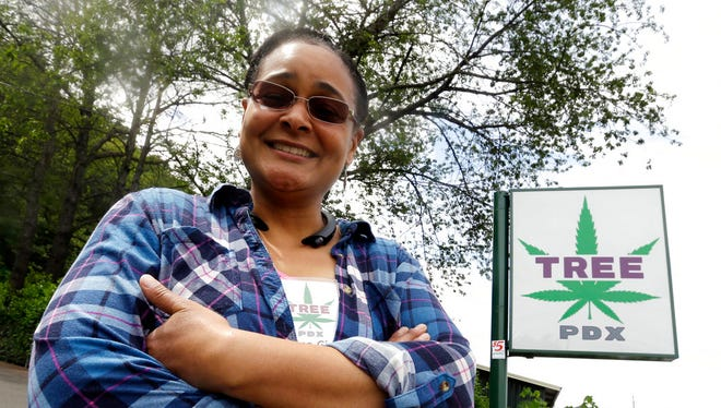 """In this Tuesday, May 29, 2018 photo, Tree PDX marijuana shop owner Brooke Smith poses for a photo outside her small shop in Portland, Ore. Smith is a member of the newly formed Oregon Craft Cannabis Alliance which will launch an ad campaign this fall to educate Oregonians about why they should pay more for """"craft cannabis"""" that's locally grown."""