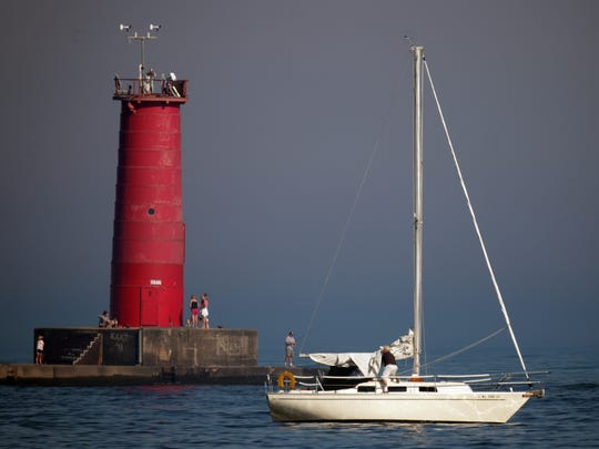A sailboat owner adjusts his sail Tuesday September 9, 2014 at the Sheboygan lakefront near the lighthouse.