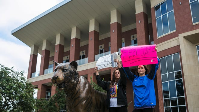 Freshman Brooke Trenthem, 19, and junior Gypsee McManus, 20, hold signs in front of University Center at the University of Memphis in October to protest the school's handling of an alleged rape off campus.