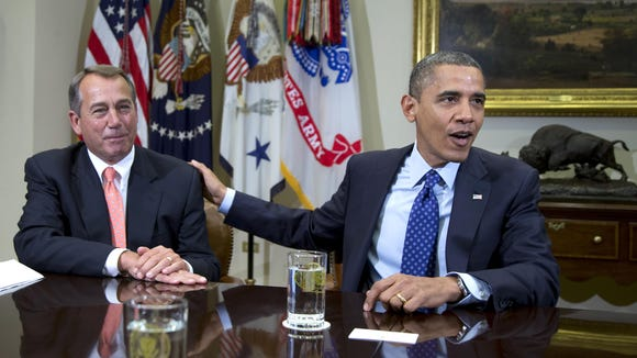 President Barack Obama acknowledges House Speaker John Boehner of Ohio while speaking to reporters in the Roosevelt Room of the White House in Washington.