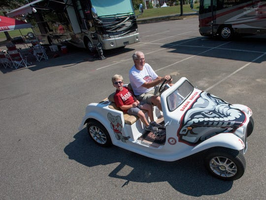 Keith Granger drives his grandson Mason Palmer in his Alabama fan car as he tailgates at his RV before the Alabama vs. Western Kentucky game in Tuscaloosa, Ala., on Saturday September 10, 2016.