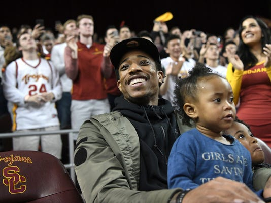 Toronto Raptors all-star DeMar DeRozan, holds his daughter Mari DeRozan and acknowledges applause while attending the Oregon against Southern California NCAA college basketball game, Thursday, Feb. 15, 2018, in Los Angeles. DeRozan played basketball at Southern California. (AP Photo/Michael Owen Baker)