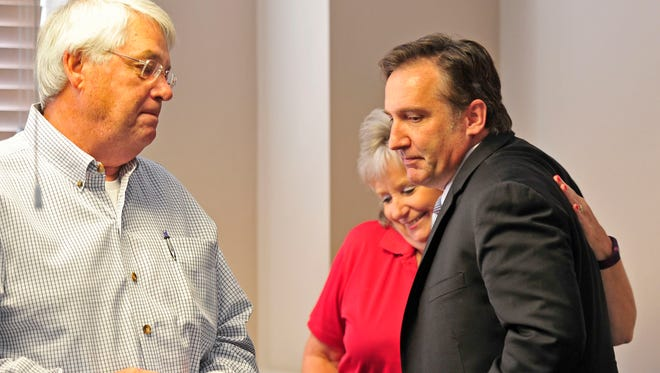 Dr. Mike Looney, right, gets a hug from Diane Giddens, Chief of Staff of Williamson County Mayor's Office, center, as Williamson County Mayor Rogers Anderson looks on during a news conference at Williamson County Schools in Franklin, Tenn., Friday, July 24, 2015.