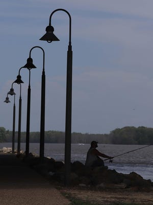 A fisherman casts his line in the Mississippi River in the shade of the Great River Bridge Tuesday on the shoreline in Burlington.