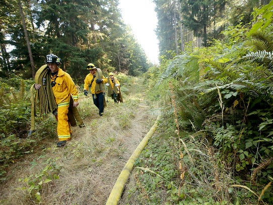 Central Kitsap and Bremerton firefighters carry hoses
