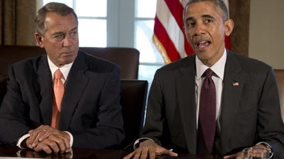 House Speaker John Boehner of Ohio listens at left as President Barack Obama speaks to media as he meets with bipartisan, bicameral leadership of Congress to discuss a wide range of issues, Tuesday, Jan. 13, 2015, in the Cabinet Room of the White House in Washington.
