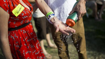 Fans try to stay hydrated and cool by spraying water on themselves and drinking water as temperatures soar at McDowell Mountain Music Festival March 29, 2015 in Phoenix, Arizona.