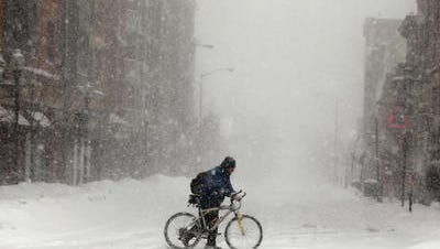 A man walks his bike across Market Street in Morristown.