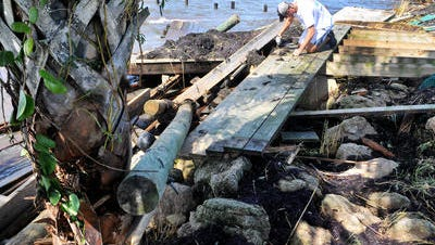 Kyle Osman of Indialantic helps frriends clear debris from the Indian River Saturday afternoon, that was once a two story boat house over the river destroyed by Hurricane Matthew, that was packing 120 mph winds, when it hit Brevard County Friday morning.