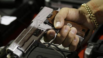 A man examines a handgun.
