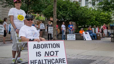 Chloe and Bill Becker of Clermont County protest Monday outside the Hamilton County Courthouse with a group of abortion opponents.