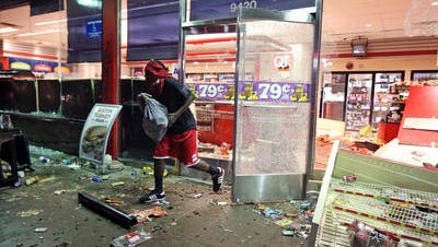 A man leaves a convenience store that was looted Aug. 10, 2014, in Ferguson, Mo.