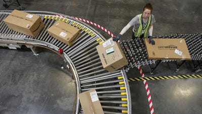 Katherine Braun sorts packages at an Amazon fulfillment center in Goodyear, Ariz.