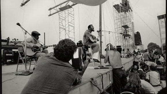 Richie Havens starting out the Woodstock festival in 1969. From the book THE ROAD TO WOODSTOCK.