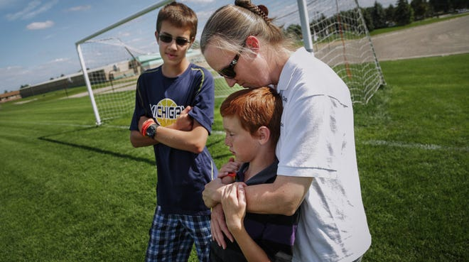 """Kris Bieniewicz of Westland, seen with her sons Josh Bieniewicz, 9, and Kyle Bieniewicz, 14, says of the incident that led to her husband's death: """"We're not going to let the evilness that took place beat us. ... We're going to persevere through it."""" They talk about her husband and their father John Bieniewicz, who died after being punched while refereeing during a soccer game in Livonia, on Wednesday August 27, 2014 at the soccer fields of Founders Sports Park in Farmington Hills where the boys both played soccer before and their father officiated matches. Ryan Garza / Detroit Free Press"""