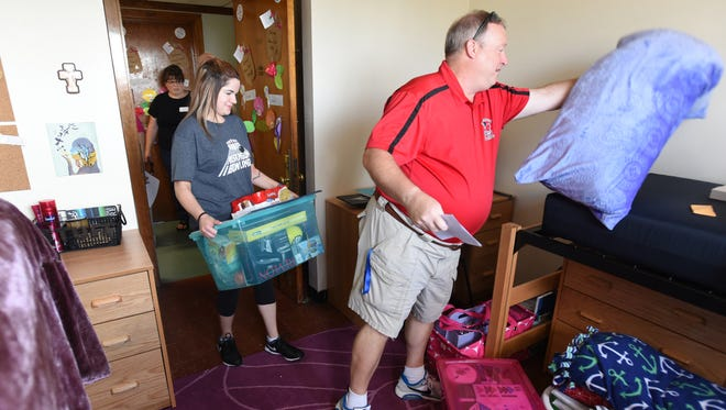Muskingum University Freshman Carmie Shook gets a little help from her bowling coach Doug Smith as she moves into Memorial Hall on Friday.