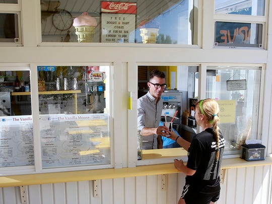 Ryan Lane hands over an ice cream shake to Autumn Petersen, 15, on June 9 at the Vanilla Moose in Aztec.