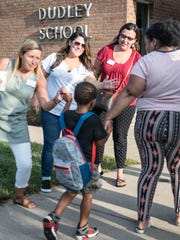 Bearcat Ambassadors, from left to right, Kathy Szenda-Wilson, Angie Layne and Maria Borden welcome back students at Dudley STEM School the first day of school on Tuesday.