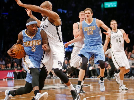 Denver Nuggets guard Ty Lawson (3) drives to the basket around Brooklyn Nets guard Jarrett Jack during the first half of an NBA basketball game Tuesday, Dec. 23, 2014, in New York. (AP Photo/Kathy Willens)