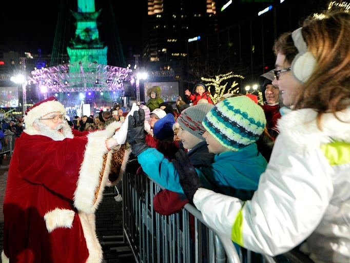 Santa greets children in the crowd during the Circle of Lights presented by Quality Connection and IBEW 481 on Monument Circle, Friday, November 29, 2013.