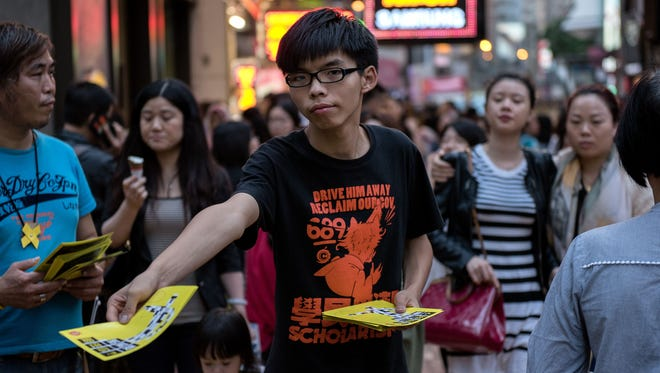 Hong Kong student leader Joshua Wong  hands out flyers in support of the Hong Kong pro-democracy protests in the Causeway Bay area of Hong Kong on Nov. 16, 2014.