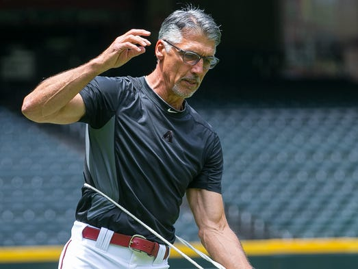 Arizona Diamondbacks first base coach Dave McKay demonstrates his Throwing Partner training ball which is attached with a rope to an armband at Chase Field on July 8, 2014.