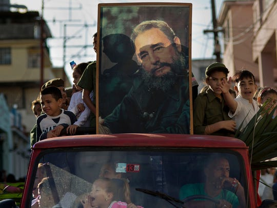Children ride in the bed of a truck with a framed image of Fidel Castro, in Regla, Cuba, Thursday, Jan. 8, 2015, in a caravan tribute to the 56th anniversary of the original street party that greeted Castro and his rebel army in 1959. Castro and his rebels arrived in Havana via caravan, after toppling dictator Fulgencio Batista. The revolutionary leader and former president has not spoken publicly on the historic Dec. 17th US-Cuba detente. (AP Photo/Ramon Espinosa)
