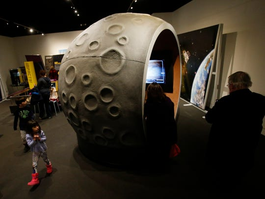 "Children gather in a hollowed-out asteroid at the ""Great Balls of Fire"" exhibition at the Delaware Museum of Natural History."