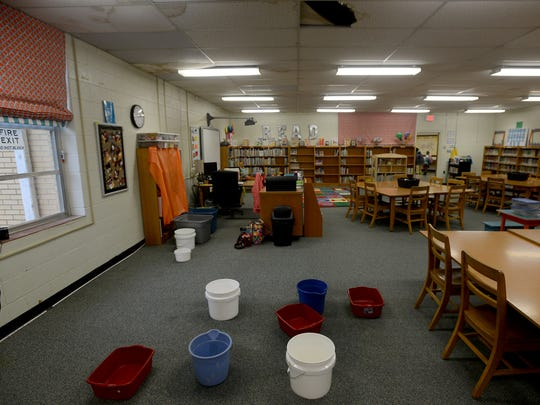 Buckets are placed on the floor in the library of Pope