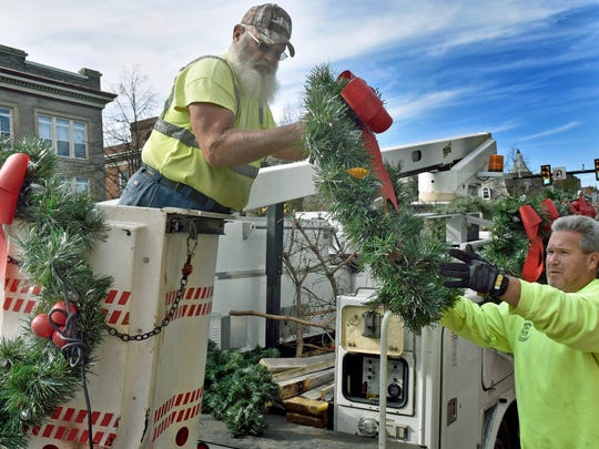 Borough of Waynesboro workers Chris Eyler, left, and Mike Benshoff are placing Christmas wreaths on light posts throughout Main Street between Broad and Grant streets on Monday, November 14, 2016.